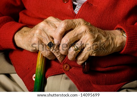 Senior Man Sitting with hands on Cane.  Rings in forefront.