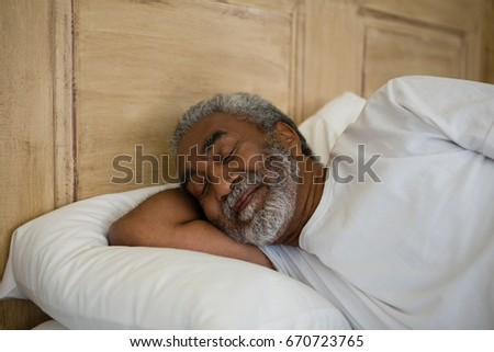 Senior man sleeping on bed in the bedroom at home