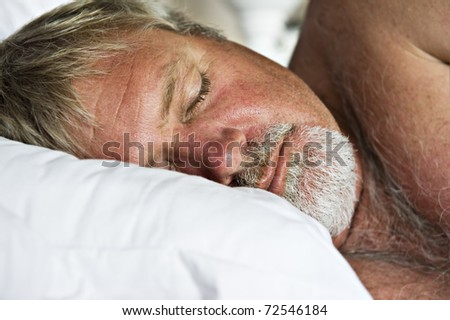 Senior man sleeping peacefully - intentional low light and shallow depth of field