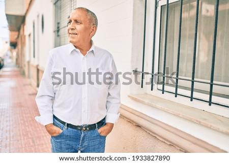 Senior man smiling happy walking at the city.