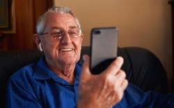 Senior man smiling on video call to family in living room
