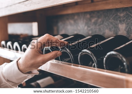 Senior man sommelier standing near cabinet touching wine bottles checking collection hand close-up Stock photo ©