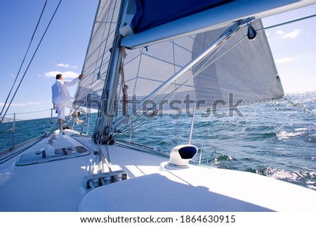 Senior man standing at the bow of a yacht out at sea and looking at the view on the horizon