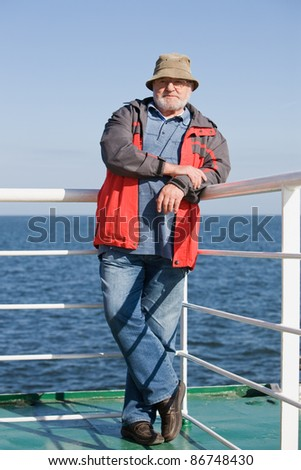 Senior man standing on ship deck