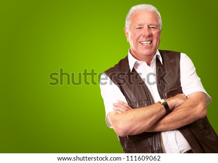 Senior Man Standing With Arms Crossed On Green Background - stock ...