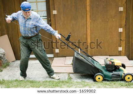 Senior man starting manually a lawn mower, focus on the tool