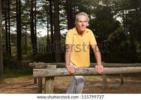 Senior man stretching his leg. Doing workout in nature. Healthy living. Forest. Outdoors. Yellow shirt and white pants. Short grey hair. #115799737