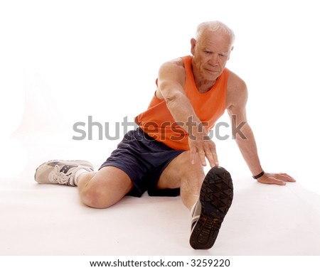 Senior man stretching on the floor before working out.