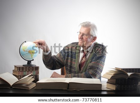 Senior man studying geography with some books and a globe