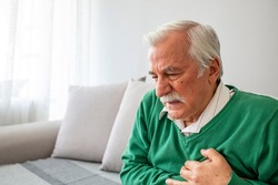 Senior man suffering from heart attack at home. Closeup shot of a mature man holding his chest in discomfort oindoors. Worried senior man feeling unwell and having chest pain in the living room.