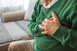 Senior man suffering from heart attack at home. Man clutching his chest. Pain, possible heart attack. Senior adult. Senior having heart attack at home. Man holding his chest in pain