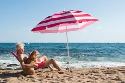Senior man sun bathing with his dog at the beach under parasol with waves, sea and sand