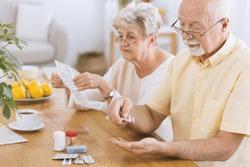 Senior man taking medication for diabetes while his wife reading a prescription