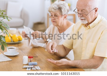 Senior man taking medication for diabetes while his wife reading a prescription