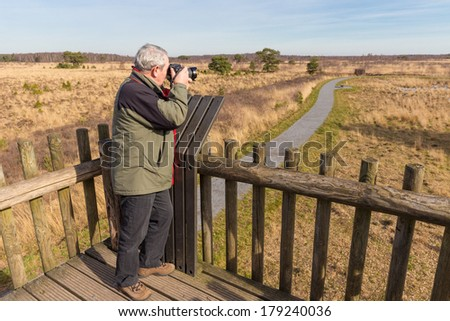 Senior man taking photos from a watch tower - stock photo