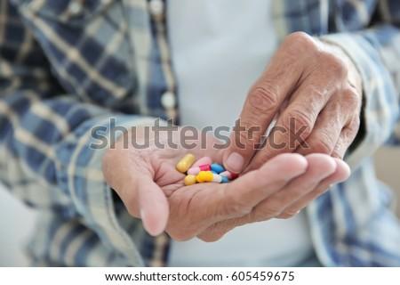 Senior man taking pills, closeup