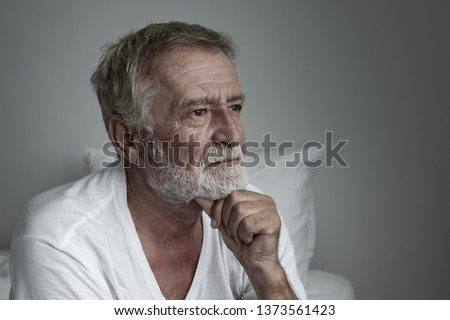 senior man thinking or try to remember alone on bed in white room #1373561423