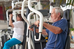 Senior man training hard at fitness gym. Caucasian pensioner training on chest press machine at fitness club. Strength fitness workout of aged people.
