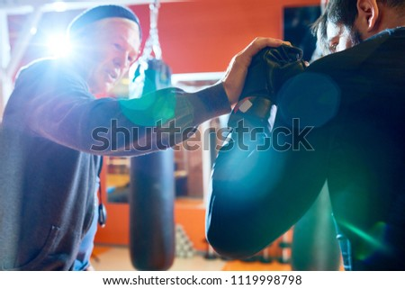 Senior man training young boxer showing him techniques and punch while working out in bright light.  #1119998798