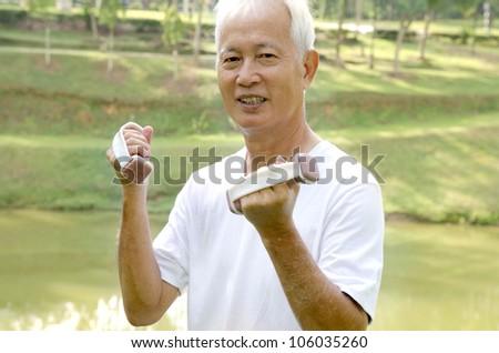 Senior man using dumbells on outdoor