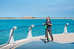 Senior man using electric scooter for transportation by the seaside