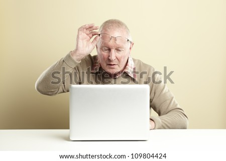 Senior man using laptop whilst looking confused