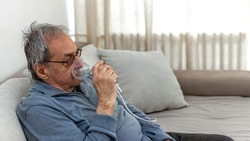 Senior man using medical equipment for inhalation with respiratory mask. Old man with serious pneumonia symptoms caused by Covid-19 virus infection sitting in home during lockdown, wearing oxygen mask