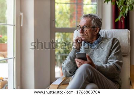 Senior man using mobile phone at home  Photo stock ©