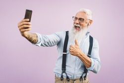 Senior man using mobile smartphone and listening music with airpods - Happy mature male having fun with new trends technology social media apps - Elderly lifestyle people and tech addiction concept