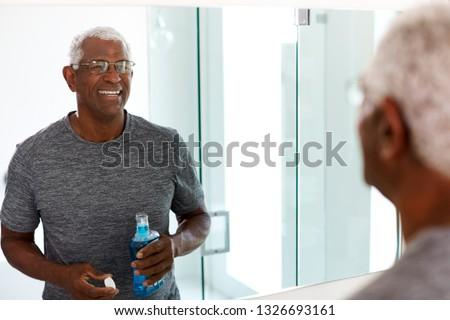 Senior Man Using Mouthwash Looking At Reflection In Bathroom Mirror Wearing Pajamas