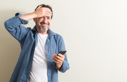 Senior man using smartphone stressed with hand on head, shocked with shame and surprise face, angry and frustrated. Fear and upset for mistake.