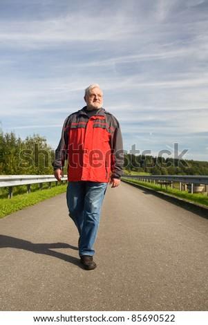 Senior man walking on road