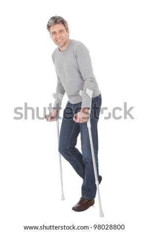 Senior man walking using crutches. Isolated on white