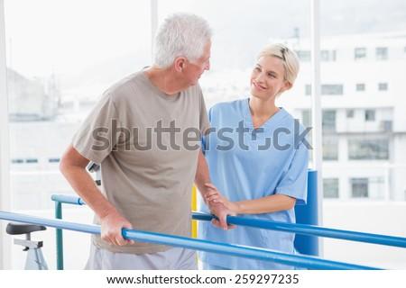 Senior man walking with therapist help in fitness studio Stock photo ©