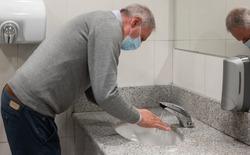 Senior man washing his hands in a public restroom, Coronavirus prevention concept