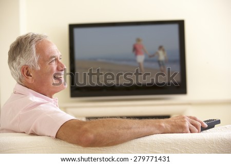 Senior Man Watching Widescreen TV At Home