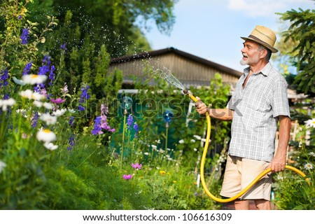 Senior man watering the garden with hose