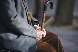Senior man with a cane sitting on wooden bench in a park.