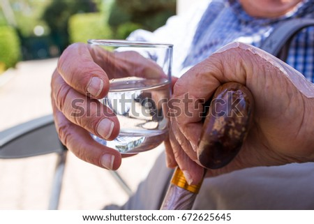 Senior man with a glass of water- Risk of Heat dehydration during summer for olders