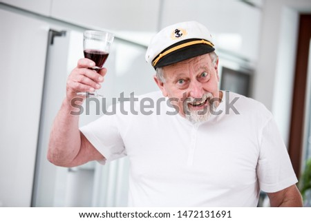 Senior man with a glass of wine in captain's cap #1472131691