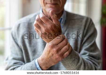 Senior man with arthritis rubbing hands  Сток-фото ©