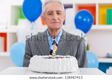 senior man with birthday cake with a question mark candle on it