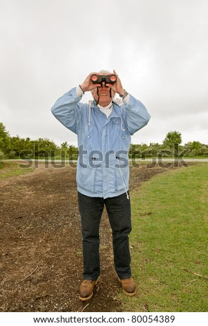 Senior man with blue jacket and binoculars outdoors on stormy day.