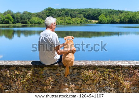 Senior man with cross breed dog sitting on wall at lake in France