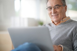 Senior man with eyeglasses connected on laptop at home