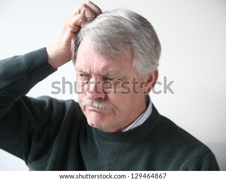 senior man with frustrated, puzzled expression scratches his head