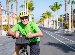 Senior man with glasses and yellow helmet riding  his bicycle in the deserted road Tenerife, Canary islands. No tourism due to Covid-19 coronavirus. Palm trees and blue sky in background