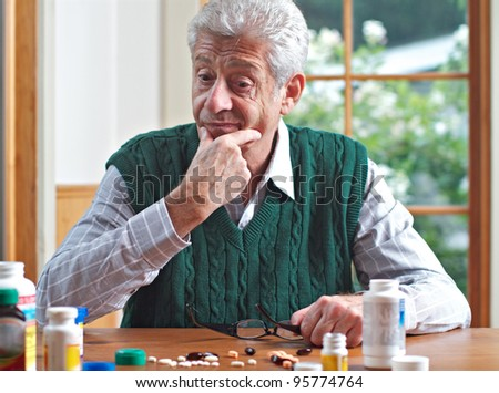 Senior man with glasses on table strokes chin and looks thoughtfully at many pills on table in front of him. Focus on man. Frontal view, green and white color palette.