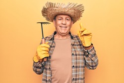Senior man with grey hair wearing gardener hat holding rake smiling with an idea or question pointing finger with happy face, number one
