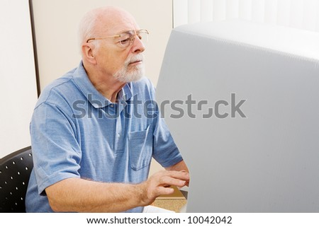 Senior man with hearing and vision impairment voting on new touch screen machine. - stock photo